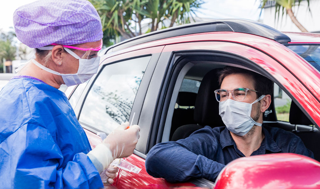 Female health worker giving Covid test to man in care - photo from Houston Methodist Medicine