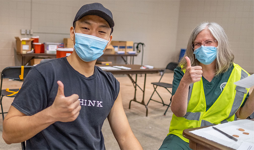 Student with thumbs up after receiving his vaccine
